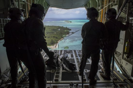Loadmasters with the 36th Airlift Squadron out of Yokota AB, Japan, watch as humanitarian assistance bundles they just airdropped parachute down to those in need during Operation Christmas Drop 2019, at Nomwin, Federated States of Micronesia, Dec. 13, 2019. Air Force photo by SrA. Matthew Gilmore.