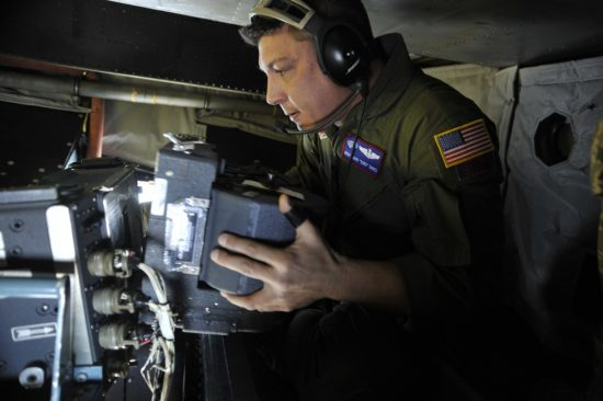 MSgt. David Dines reloads the film magazine on a panoramic camera Jan. 16, 2010, while flying over Haiti on an OC-135B observation aircraft. Air Force photo by SrA. Perry Aston.